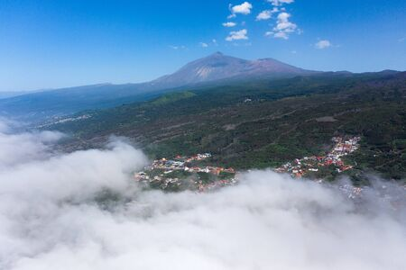 View from the height on Teide National Park and village, landscape above the clouds, rich coniferous vegetation. Tenerife, Canary Islands, Spain