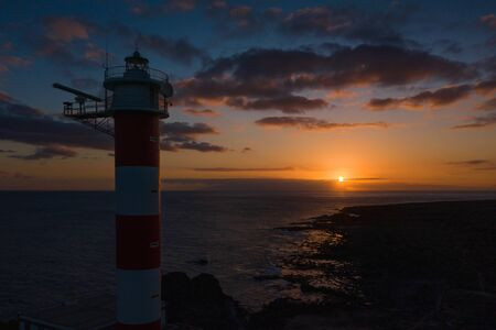 Aerial view of the lighthouse silhouette Faro de Rasca at sunset on Tenerife, Canary Islands, Spain. Wild Coast of the Atlantic Ocean