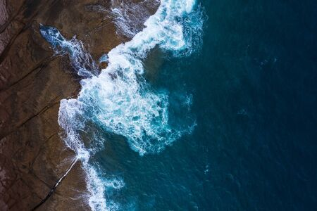 Top view of a deserted coast. Rocky shore of the island of Tenerife, Canary Islands, Spain. Aerial drone photo of ocean waves reaching shore Imagens