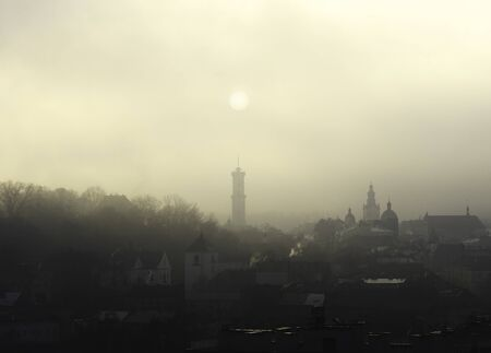 Historic center of Lviv, Ukraine in dense fog. Silhouette of the sun over the town hall