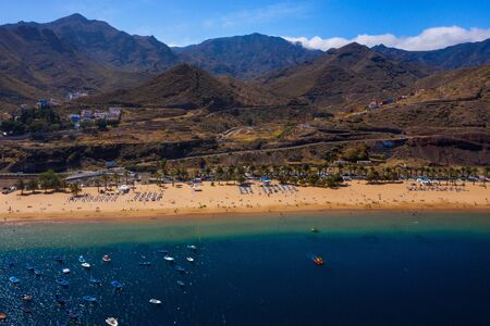 Aerial view of the golden sand, palm trees, sun loungers, unrecognizable people on the beach Las Teresitas, Tenerife, Canaries, Spain