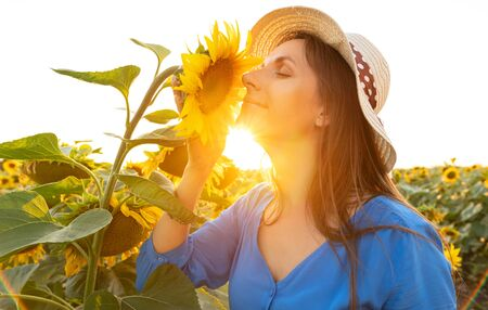 Woman in a blue dress and hat sniffs  a sunflower in the field at sunset. Agriculture. Harvesting Imagens