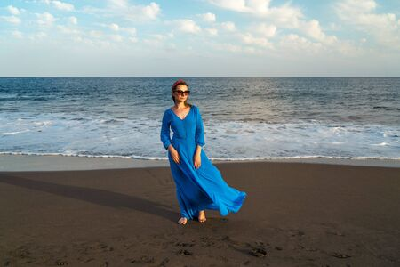Woman in sunglasses and beautiful blue dress on a black volcanic beach. Atlantic coast, Tenerife island, Canary islands, Spain