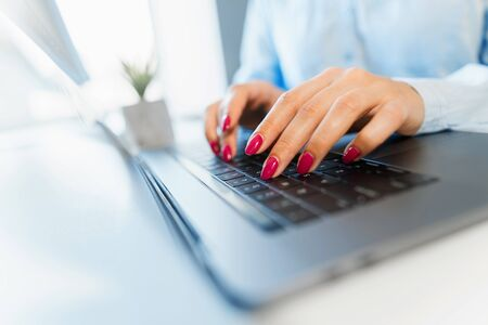 Female hands with bright manicure are typing on a laptop keyboard Imagens