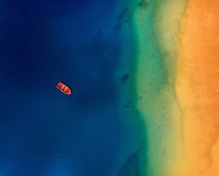 Top view of a lonely red boat anchored off the coast of Las Teresitas beach. Tenerife, Canaries, Spain