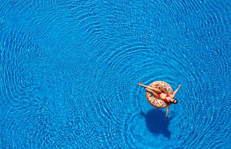 Aerial view of a woman in red bikini lying on a donut in the pool. Concept of summer rest and relaxation