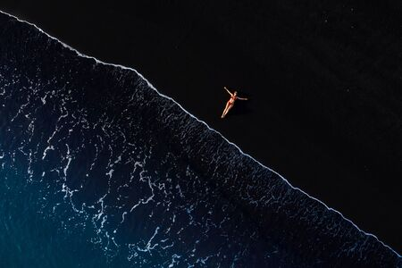 Aerial view of a woman in a red swimsuit lying on a black beach on the surf line. Coast of the island of Tenerife, Canary Islands, Spain. Imagens