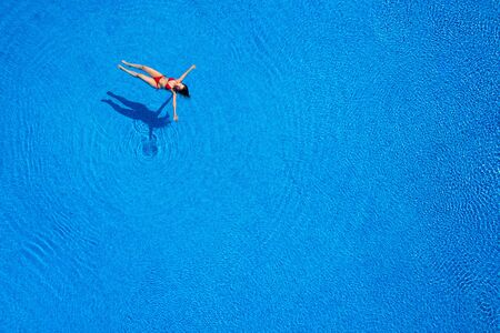 Aerial view of a woman in a red swimsuit lying on her back in the pool. Relaxing concept Imagens