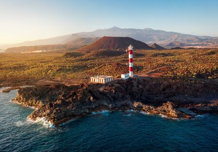 Aerial view of the lighthouse Faro de Rasca at sunset on Tenerife, Canary Islands, Spain. Wild Coast of the Atlantic Ocean