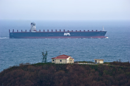 Large container ship APL SOUTHAMPTON passes not far from the cape. Nakhodka Bay. East (Japan) Sea. 05.05.2014