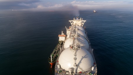 Top view of a large LNG tanker and a tanker standing side by side.