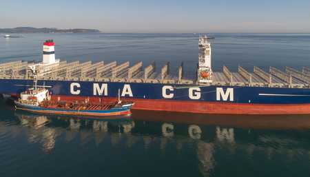 russkiy: Nakhodka. Russia - July 29, 2017: Bunkering tanker Ostrow Russkiy a large container ship CMA CGM J. Adams.