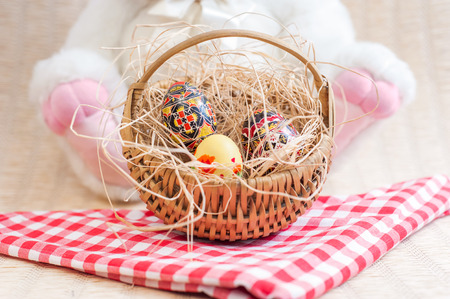 hamper: Easter eggs in straw basket and cute bunny on background
