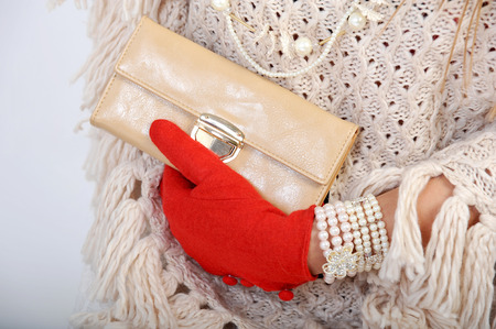 jewellry: Elegant woman hand with beige wallet and red gloves