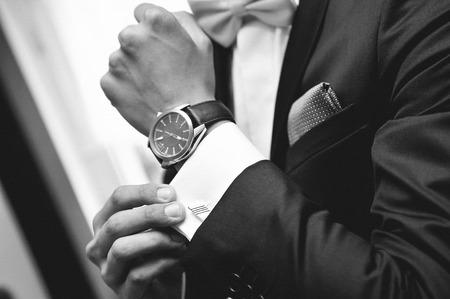 우아한 배경: 손에 양복과 시계를 가진 남자