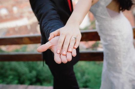 Bride and groom holding wedding ring in hand photo