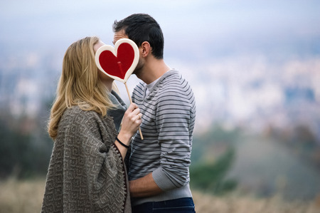 Young couple kissing and holding a candy heart Stockfoto