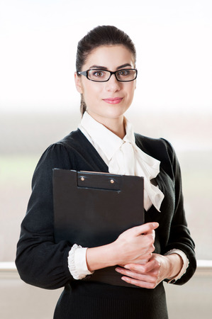 signing authority: Beautiful young businesswoman with black dress and eye glasses smiling