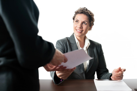 Business woman in grey suit sitting at desk and coworker giving her a paper to sign photo