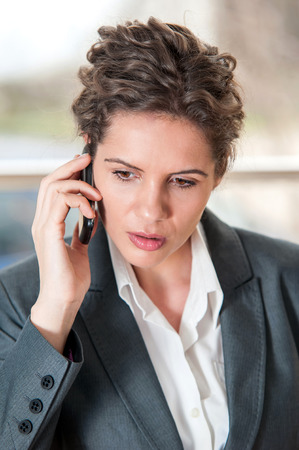 Young business woman looking worried while talking on mobile phone photo