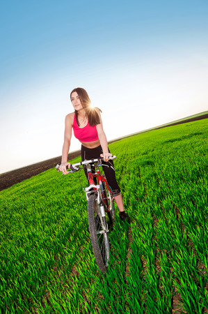 Woman cycling in the green grass and blue sky background photo