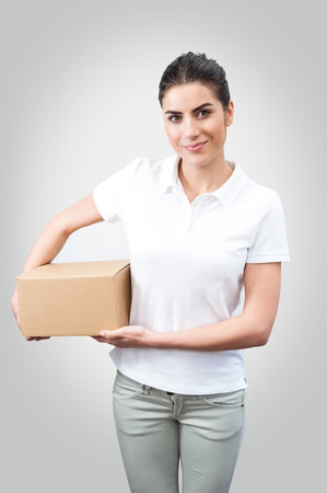 Delivery person delivering packages holding cardboard box, smiling happy in uniform  Beautiful young woman professional courier isolated on white background  Standard-Bild
