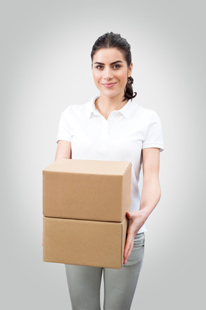 Delivery person holding packages,cardboard box  Woman courier smiling happy isolated on white background  Beautiful young female professional Post, package and delivery concept