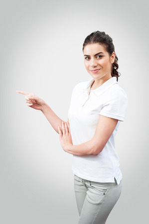Beautiful casual woman pointing above presenting isolated on a white background  series