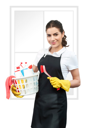 Spring cleaning Woman with black apron holding a red Cleaning Brush in left hand and a basket full of cleaning products in right hand  Fake window on background,white background photo