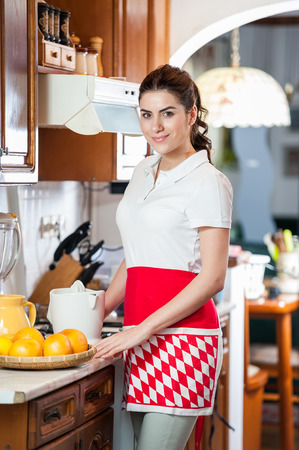 juice squeezer: Young woman in the kitchen with red apron next to the juice squeezer and a bowl of grapefriut  Stock Photo