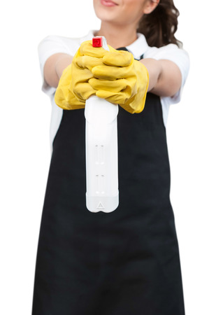 Closeup of a Spring cleaning Woman with black apron and yellow gloves, pointing a spray bottle at the camera on a white background photo