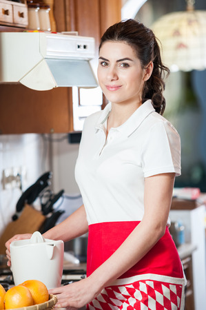 juice squeezer: Young woman in the kitchen with red apron next to the juice squeezer and a bowl of grapefriut  Closeup