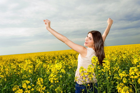 Young woman standing in yellow rapeseed field raising her arms expressing happiness and freedom  Blue sky background