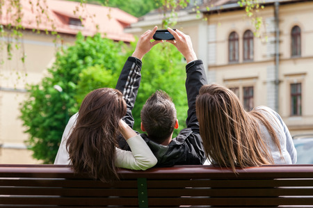 Outdoor portrait of group of friends taking photos with a smartphone in the park sitting on a bench back view  photo