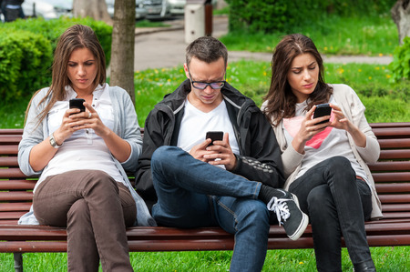 cell phone: Group of friends two women and one man, sitting on a bench in park separately looking at their phones loosing communication  people using their phones and sending texts as they stand beside each other