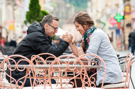 Young couple sitting by the table at street coffee shop terrace, playing, talking, having fun laughing smiling happy  photo