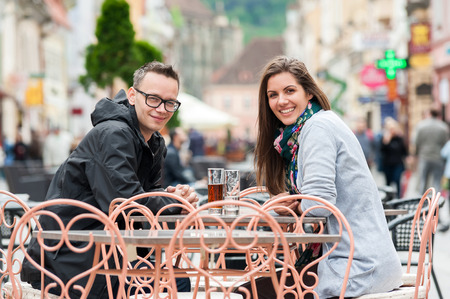 Young couple smiling in a street coffee shop terrace drinking, talking, having fun laughing smiling happy  photo