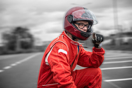 Formula driver posing in dramatic sky background, outdoor, wearing protective helmet and red racing suit