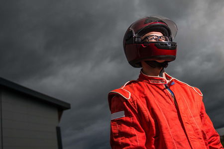 Closeup race car driver wearing protective helmet and red racing suit