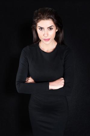 Junge Geschäftsfrau, ernsten vor schwarzem Hintergrund in eleganten schwarzen engen Kleid Arme verschränkt Weibliche Modell Isolated