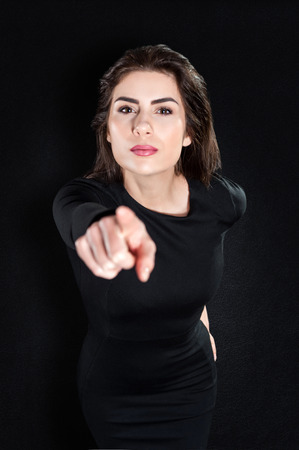 annoy: Closeup portrait of serious young woman pointing at someone,blaming a person, isolated on black background in elegant black tight dress   Human emotions, facial expressions, feelings