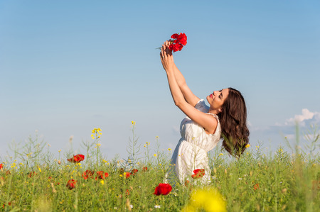 light hearted: Portrait of beautiful young woman with poppies in the field with a poppies bouquet Stock Photo