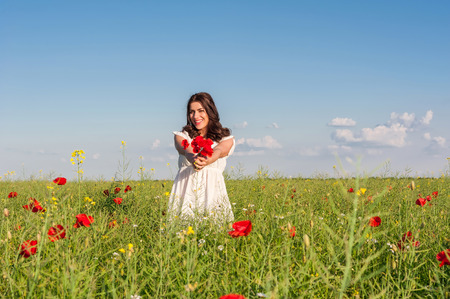 Beauty woman in poppy field in white dress in a sunny summer day holding a poppies bouquet Stock fotó