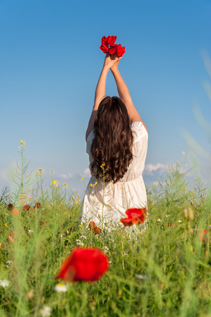 Young girl on a poppy field,back view, summer outdoor  Freedom concept  Series  Free Happy Woman Enjoying Nature photo