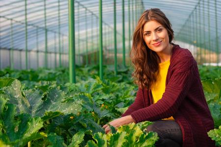 Mooie jonge vrouw tuinieren en lacht naar de camera. Kas producten. Voedselproductie.