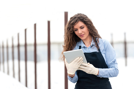 Female researcher technician studying with a tablet and gloves, dressed in office clothes,office shirt and apron in all withe greenhouse. Stock fotó