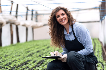 grow food: Beautiful young biotechnology woman engineer with clipboard and pen, writing and examining plants for disease in greenhouse with apron and gloves. Greenhouse produce. Food production.