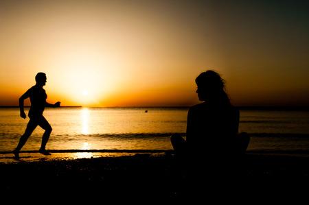 Silhouette junge Frau praktizieren Yoga am Strand bei Sonnenaufgang und ein alter Mann am Strand laufen