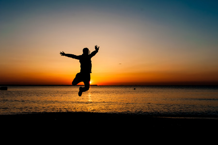 human energy: Silhouette of jumping man on sunrise background