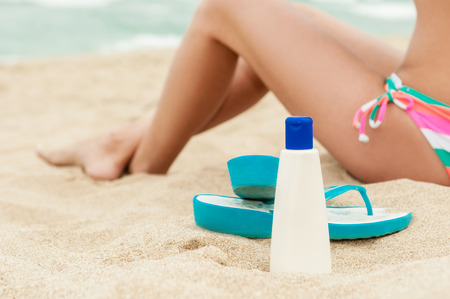 lotion bottle: Woman applying sun protection lotion. Bottle of sun protection lotion and flip flops. Close-up, no face!